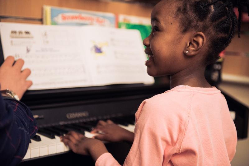 Criança sorri para sua professora ao tocar o piano em sua frente.